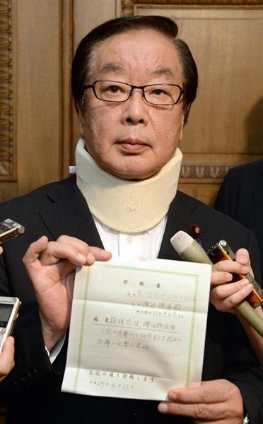 頸椎捻挫の診断書を手に記者団の取材に応じる渡辺博道厚労委員長=12日午後、国会内
